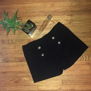 Black fitted shorts with gold buttons